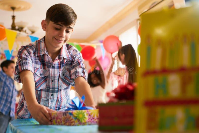 Barn som hemma sätter gåva på tabellen under födelsedagpartiet royaltyfri foto