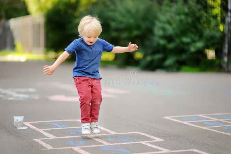 Barn som hoppar hage på lekplats utomhus på en solig dag royaltyfri bild