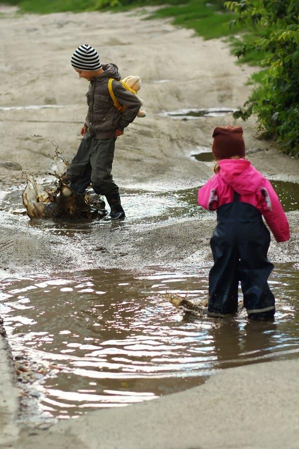 Barn som hoppar och plaskar i leriga pölar fotografering för bildbyråer