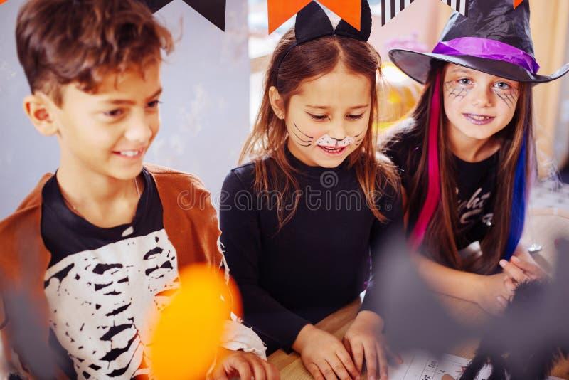Barn som känner sig underhöll, medan bära allhelgonaaftondräkter i dagis arkivbild
