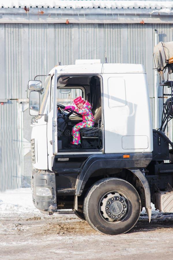 Barn som kör en lastbil Lekar för ett barn i lastbilsföraren barnet vänder hjulet av en stor lastbil arkivfoto