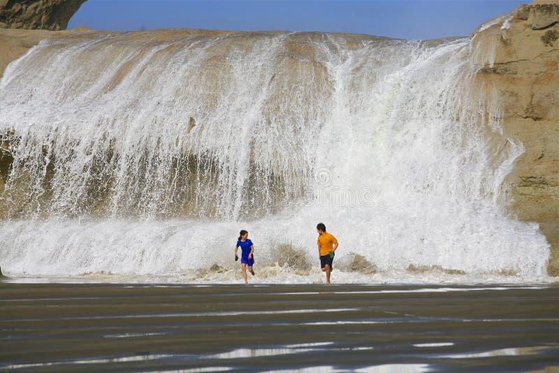 Barn som kör från vatten som över kraschar, vaggar arkivfoto