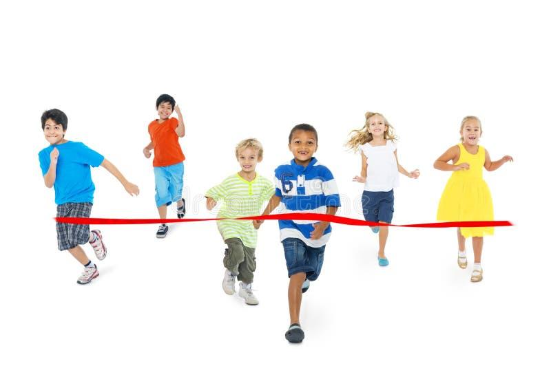 Barn som kör in mot mållinjen arkivbilder