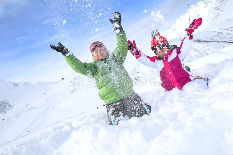 Barn som kastar det insnöat luften arkivbild