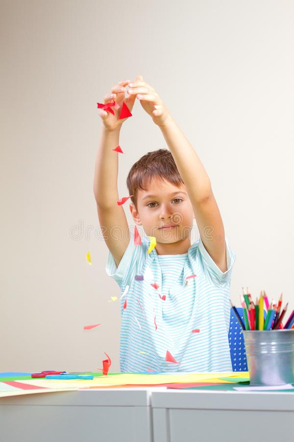 Barn som kastar det lilla stycket av kulört papper som konfettier, efter han skapade hälsningkortet arkivfoto