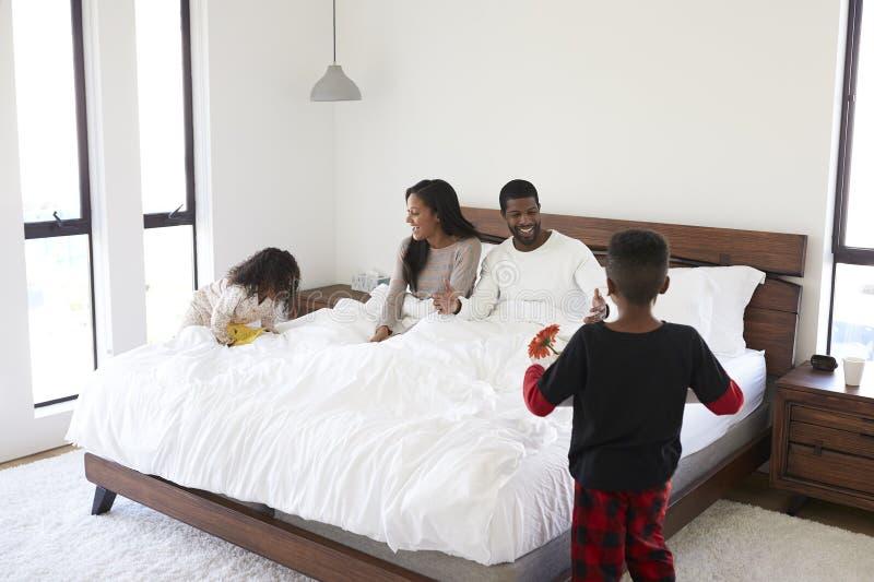 Barn som kommer med föräldrar, frukosterar i säng för att fira dag eller födelsedag för fäder för moderdag arkivbilder