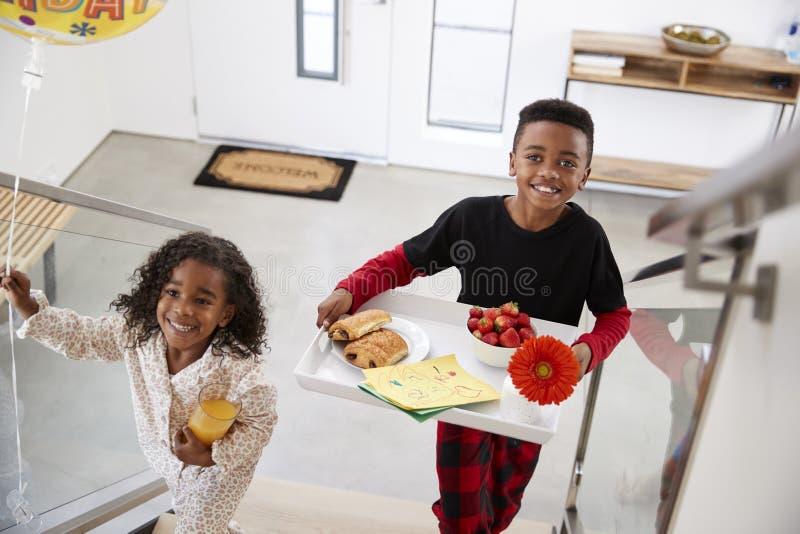 Barn som kommer med föräldrar, frukosterar i säng på dag för Tray To Celebrate Birthday Mothers dagfäder royaltyfria bilder
