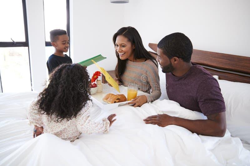 Barn som kommer med moderfrukosten i s?ng f?r att fira moderdag eller f?delsedag arkivfoton