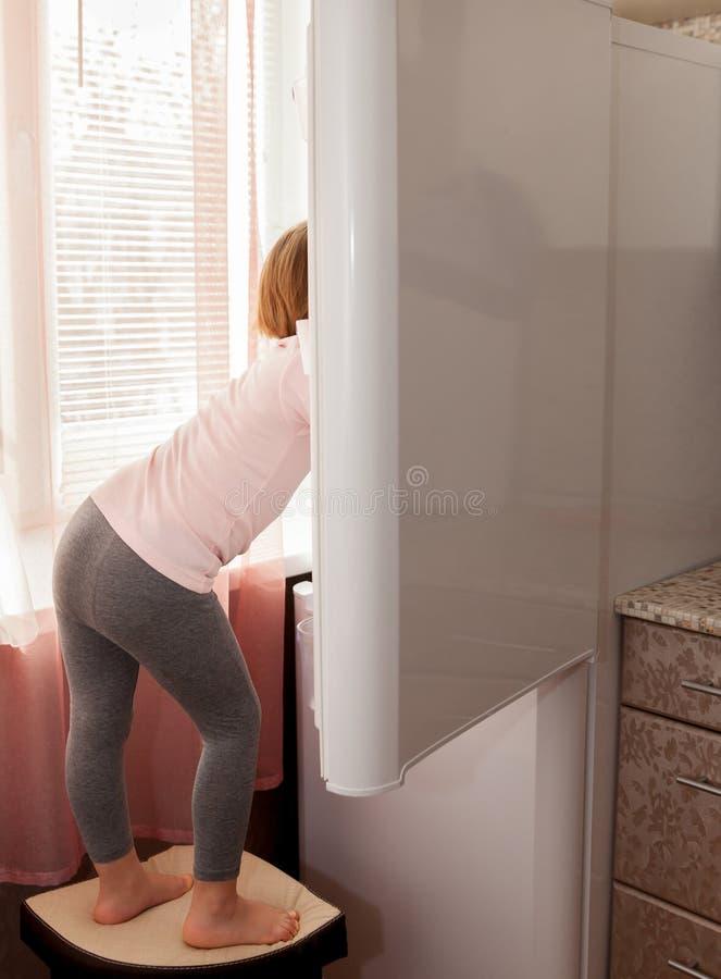 Barn som kontrollerar kylen i kök royaltyfri bild