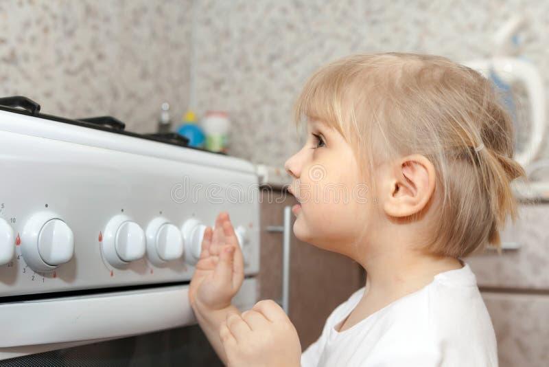 Barn som kontrollerar ugnen på inhemskt kök royaltyfria bilder