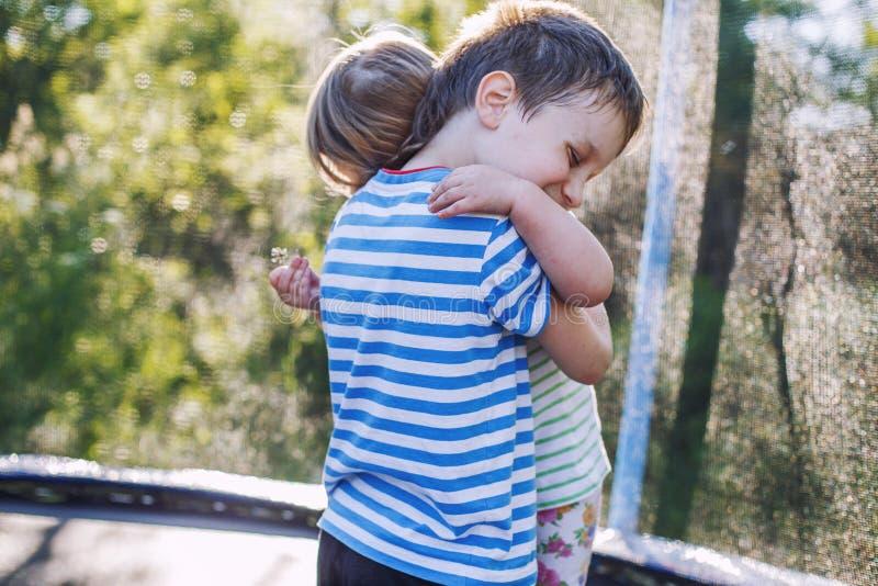 Barn som kramar i trädgården på trampolinen Broder med hans lilla syster arkivbild