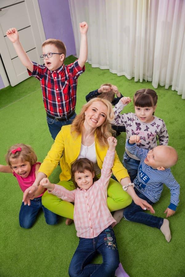 Barn som kramar läraren royaltyfri foto