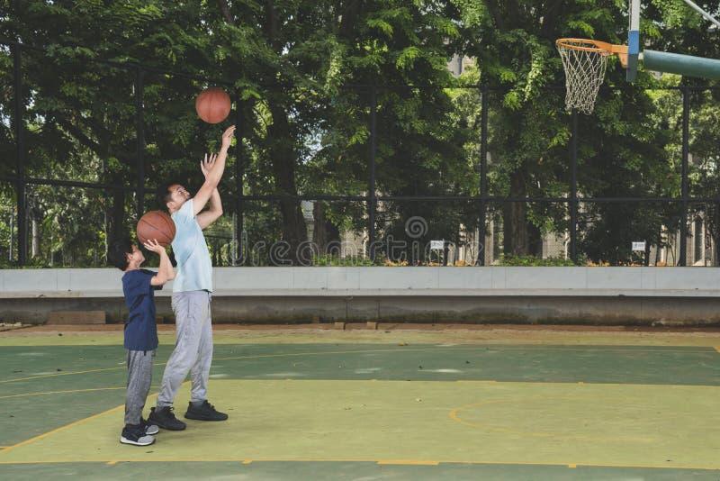 Barn som lär att skjuta en basket med hans fader arkivbilder
