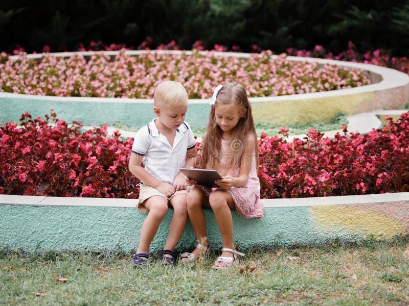 Barn som lär en digital minnestavla och sitter i parkera En pojke och en flicka som spelar i en grej på en naturlig bakgrund royaltyfri bild