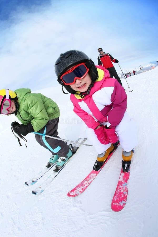 Barn som lär hur man skidar med familjen fotografering för bildbyråer
