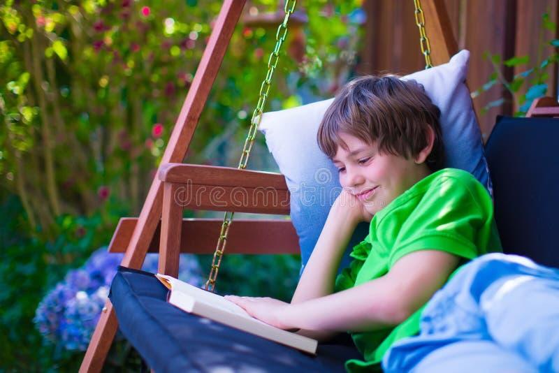 Barn som läser en bok i trädgården royaltyfri foto