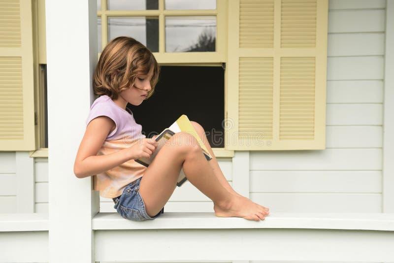 Barn som läser en bok på balkongen royaltyfri fotografi