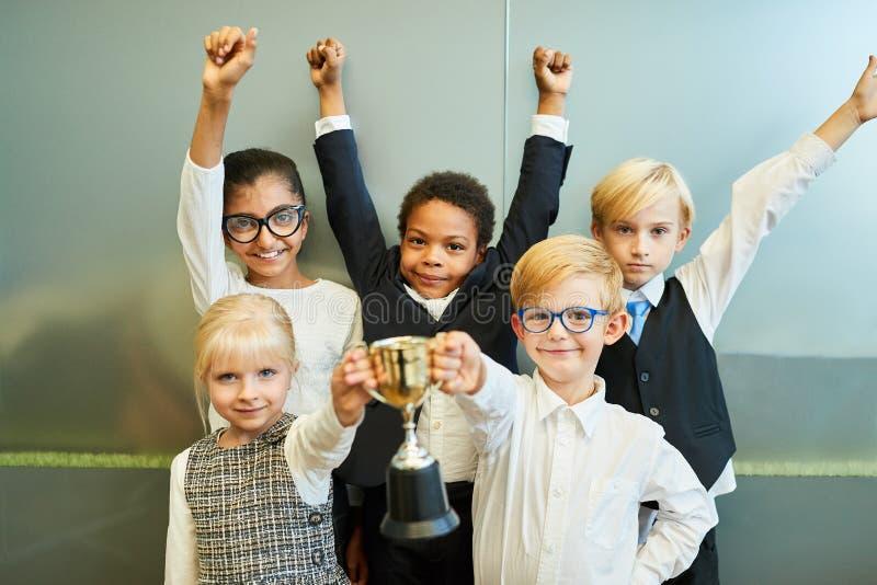Barn som laget för affärsstart med vinnares trofé royaltyfri bild