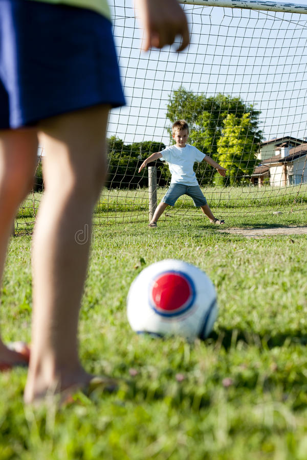 barn som leker fotboll arkivbild