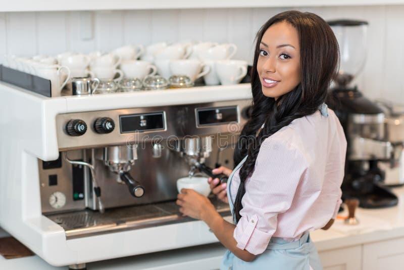 Barn som ler afro amerikanskt baristadanandekaffe genom att använda kaffemaskinen i kafé royaltyfria foton