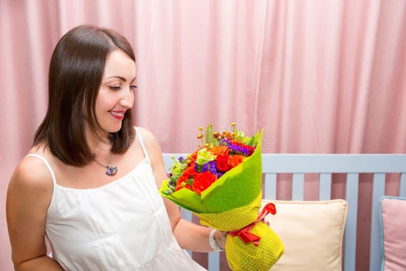 Barn som ler den härliga kvinnan med en bukett av blommor på födelsedagen Stående i ett kafé royaltyfri foto
