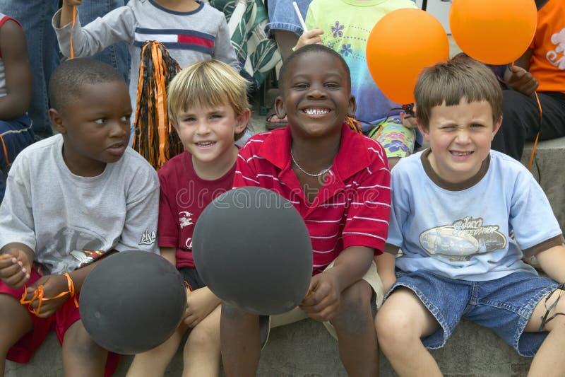 Barn som ler och rymmer ballonger royaltyfri foto
