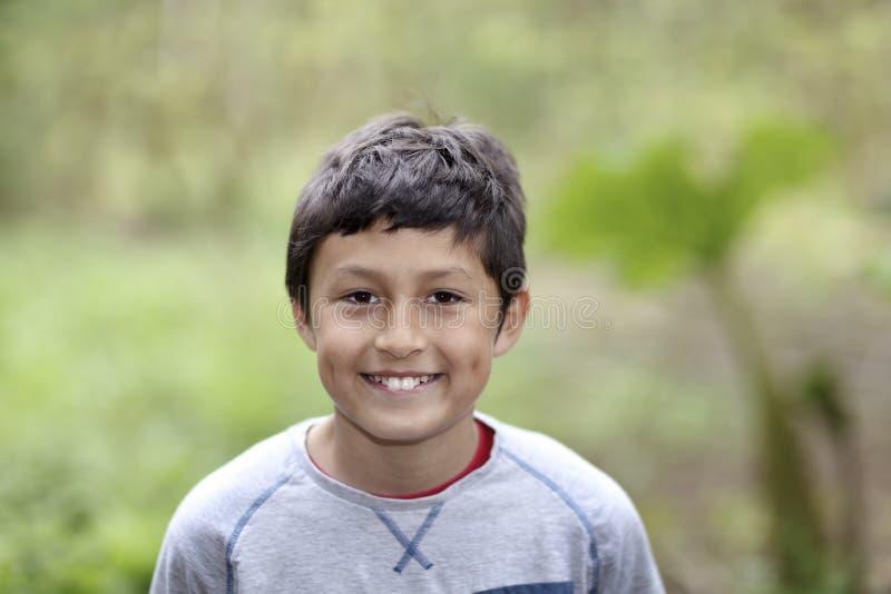 Barn som ler pojken för blandat lopp i trän arkivfoton