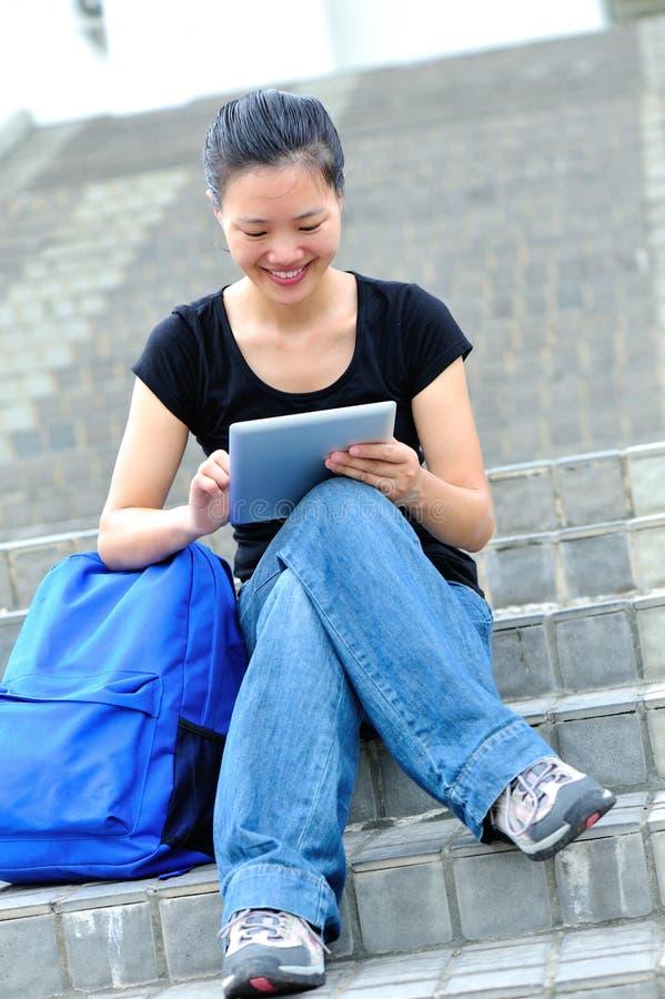 Barn som ler studenter som använder en digital minnestavla royaltyfri bild