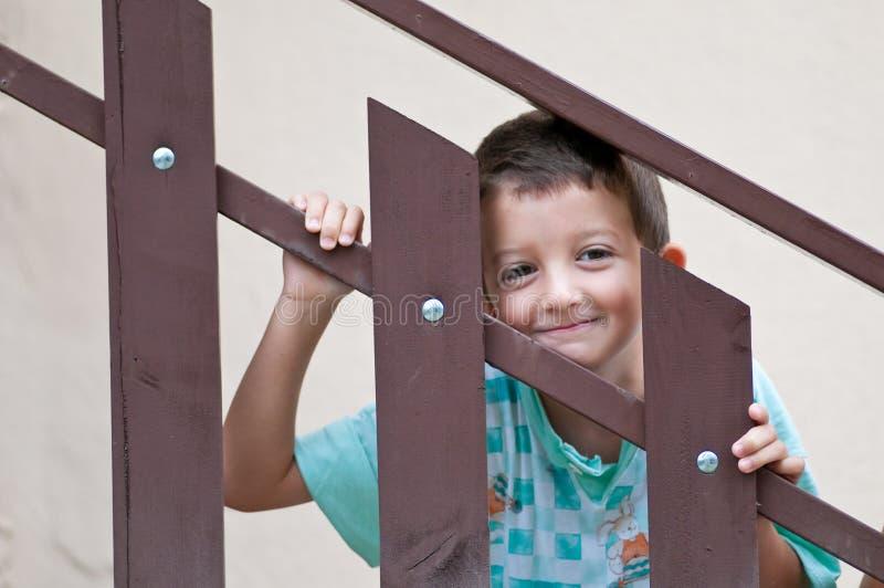 Barn som ler till och med en räcke royaltyfri bild