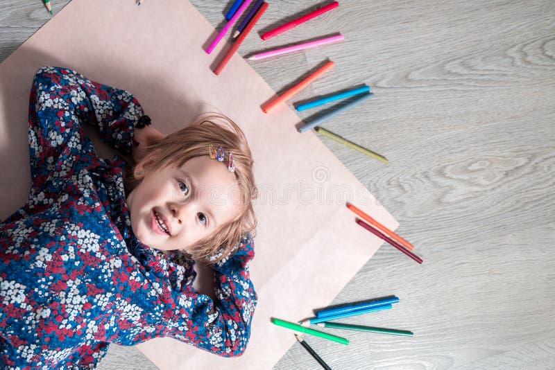 Barn som ligger på det pappers- golvet se kameran nära färgpennor Liten flickamålning, teckning Top beskådar lego för hand för by arkivbild