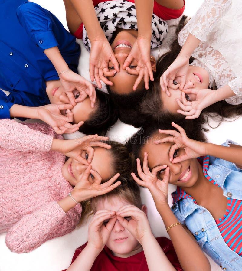 Barn som ligger på golvhuvudet - - head med exponeringsglas ut ur fingrar arkivbild