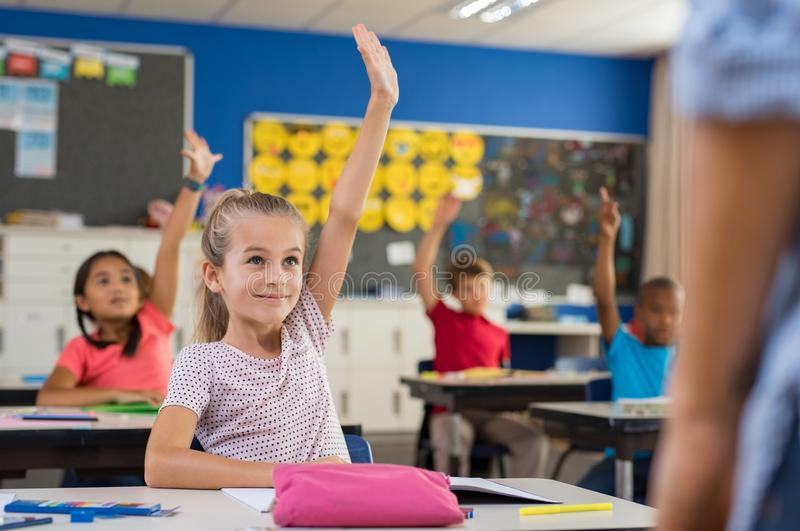 Barn som lyfter händer i klassrum arkivfoton