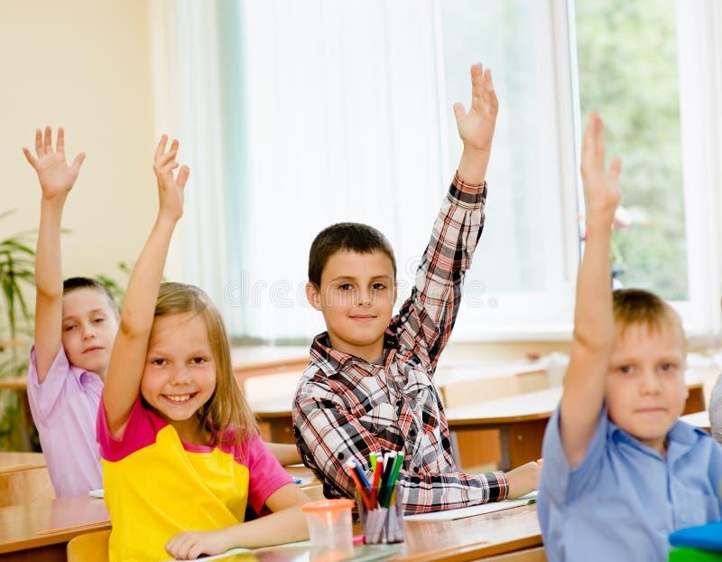 Barn som lyfter händer som vet svaret till frågan royaltyfria bilder