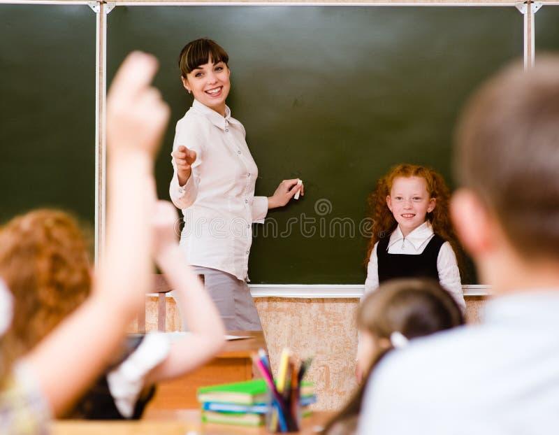 Barn som lyfter händer som vet svaret till frågan arkivbild
