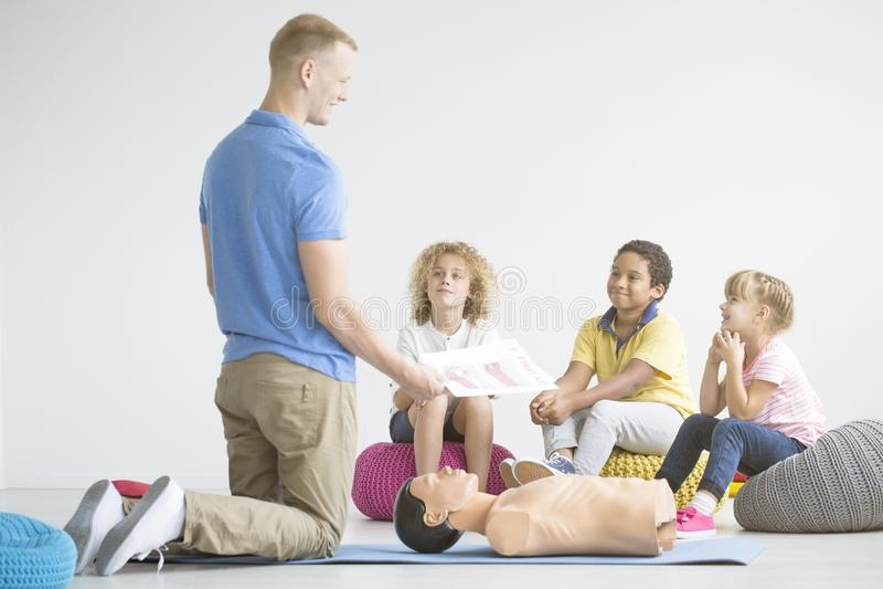 Barn som lyssnar till personen med paramedicinsk utbildning fotografering för bildbyråer