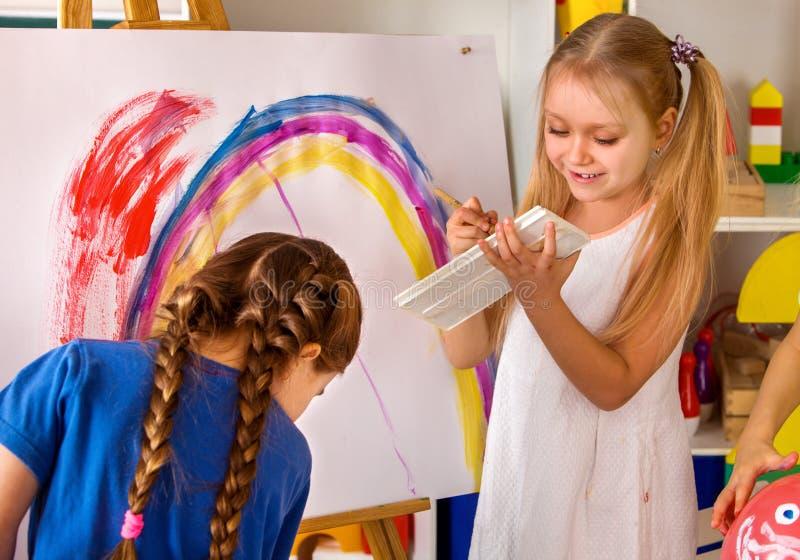 Barn som målar fingret på staffli Grupp av ungar med läraren arkivbild