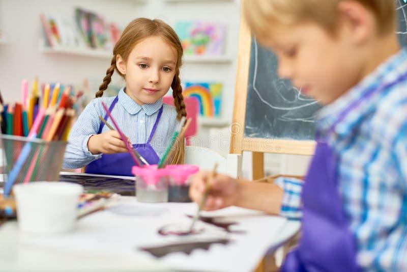 Barn som målar i Art Class av utvecklingsskolan royaltyfria foton