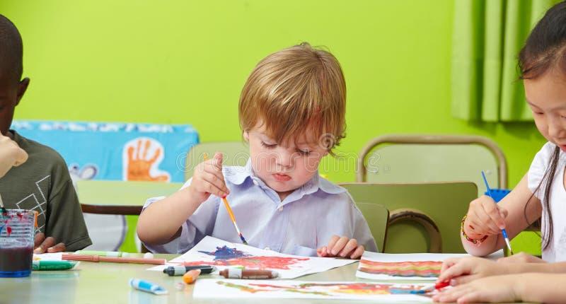 Barn som målar i dagis arkivbilder