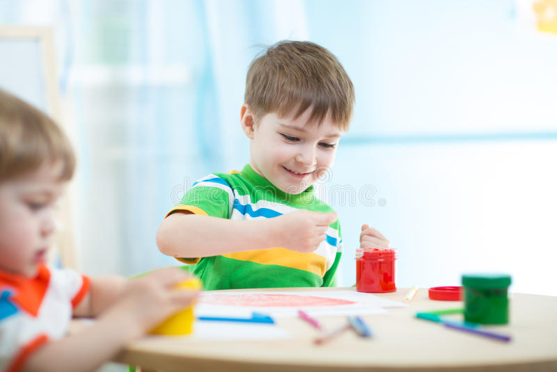 Barn som målar i daycare eller barnkammare fotografering för bildbyråer