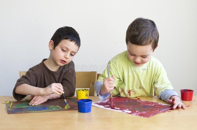 Barn som målar med färger royaltyfria foton