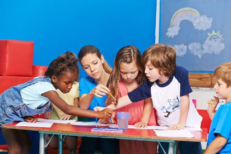 Barn som målar med vattenfärg i dagis royaltyfria bilder