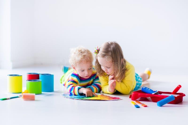 Barn som målar väggar omdanar hemma royaltyfri fotografi