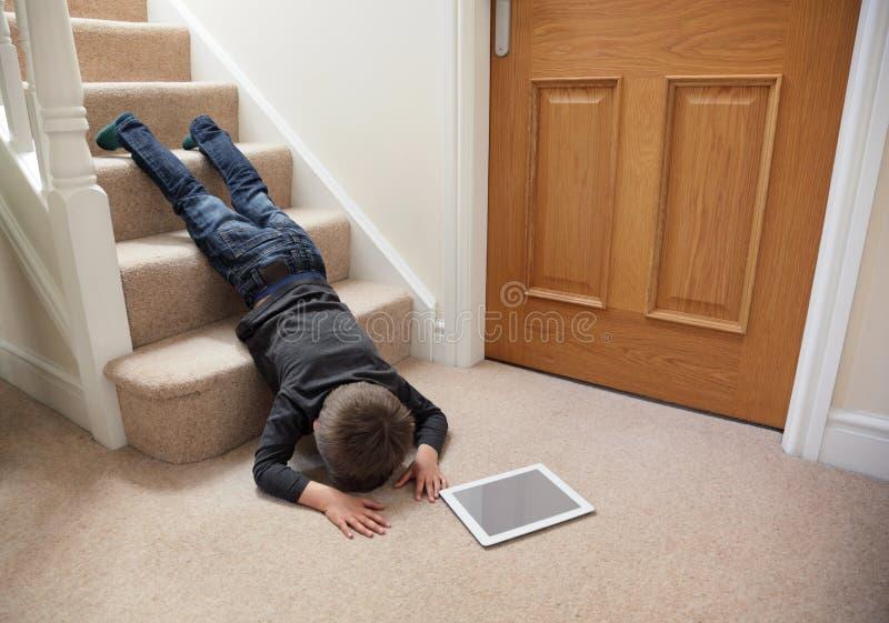 Barn som ner faller trappan arkivfoto