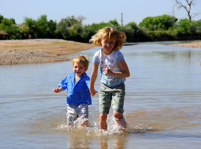 barn som paddlar floden royaltyfri bild