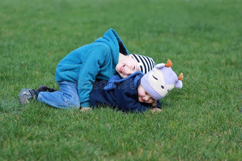 Barn som palying och att ha gyckel och att ligga på gräset som skrattar royaltyfri foto