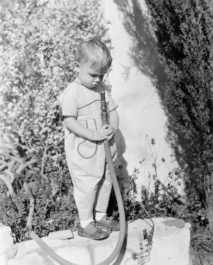 Barn som pekar slangen på framsidan (alla visade personer inte är längre uppehälle, och inget gods finns Leverantörgarantier att  arkivbild