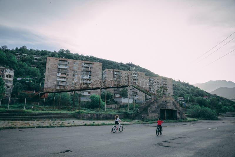 Barn som rider cyklar i en f?rorts- stad, parkerar royaltyfria bilder