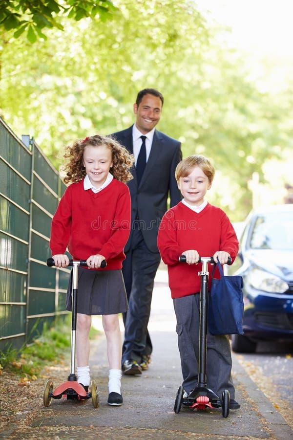 Barn som rider sparkcyklar på deras väg till skolan med fadern royaltyfri bild