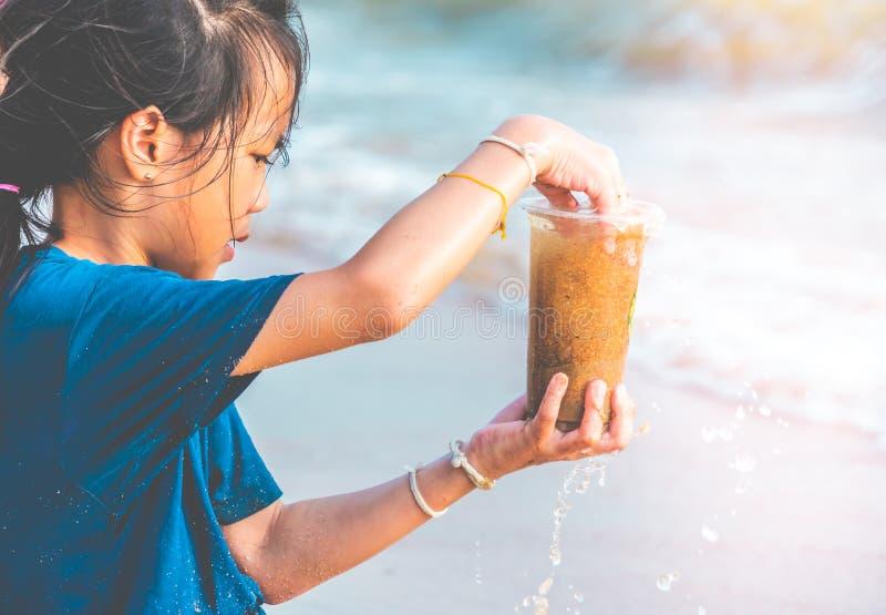 Barn som rymmer den plast- flaskan som han grundar upp på stranden för miljö- rent begrepp royaltyfri foto