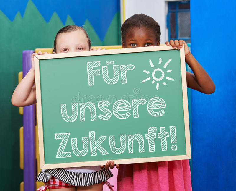 Barn som rymmer den svart tavlan med tysk slogan arkivbilder